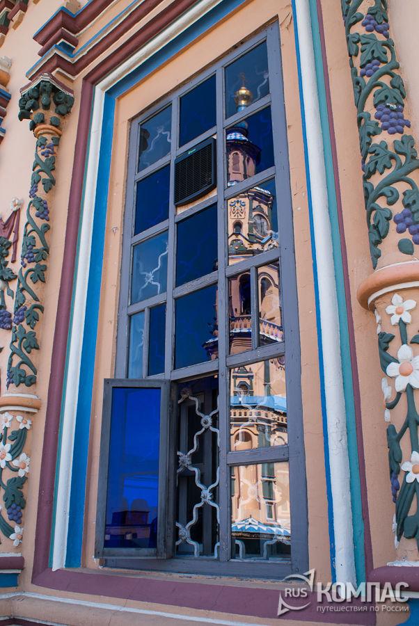 Отражение колокольник в окне Петропавловского собора