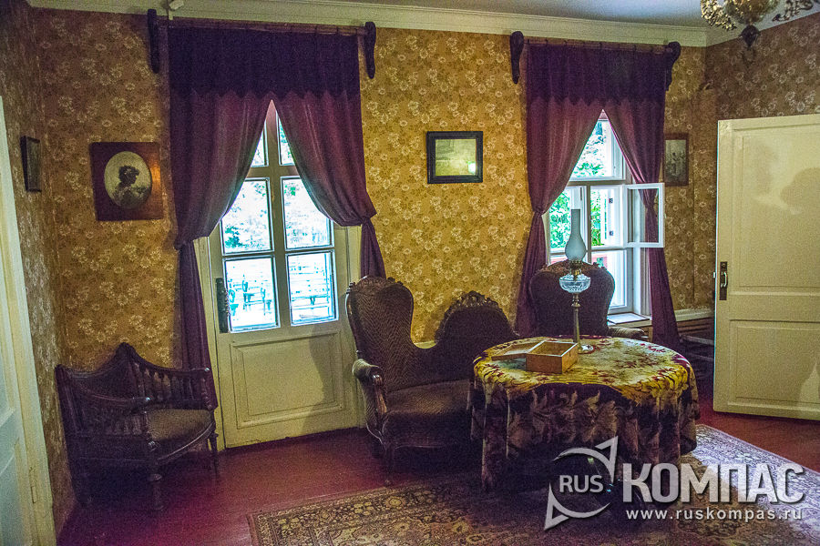Круглый стол, уютные диванчик и кресло в гостиной