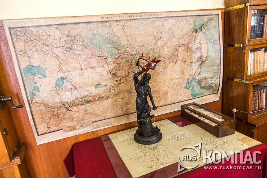 """Лампа-статуэтка """"Коваль мира"""" стоит у настенной карты"""